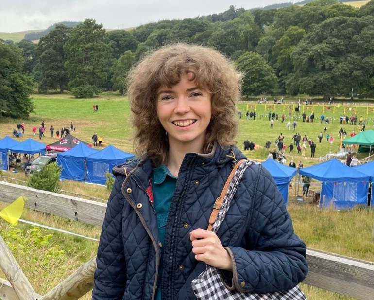 Claire faces the camera smiling. In the background a festival is taking place - groups of people are in a field surrounded by stalls