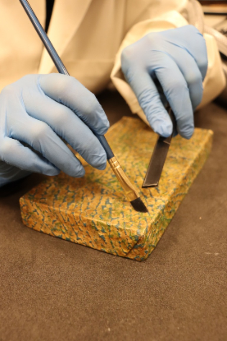 Curators wears blue gloves and cleans a card box using a fine dry brush and vacuum nozzle