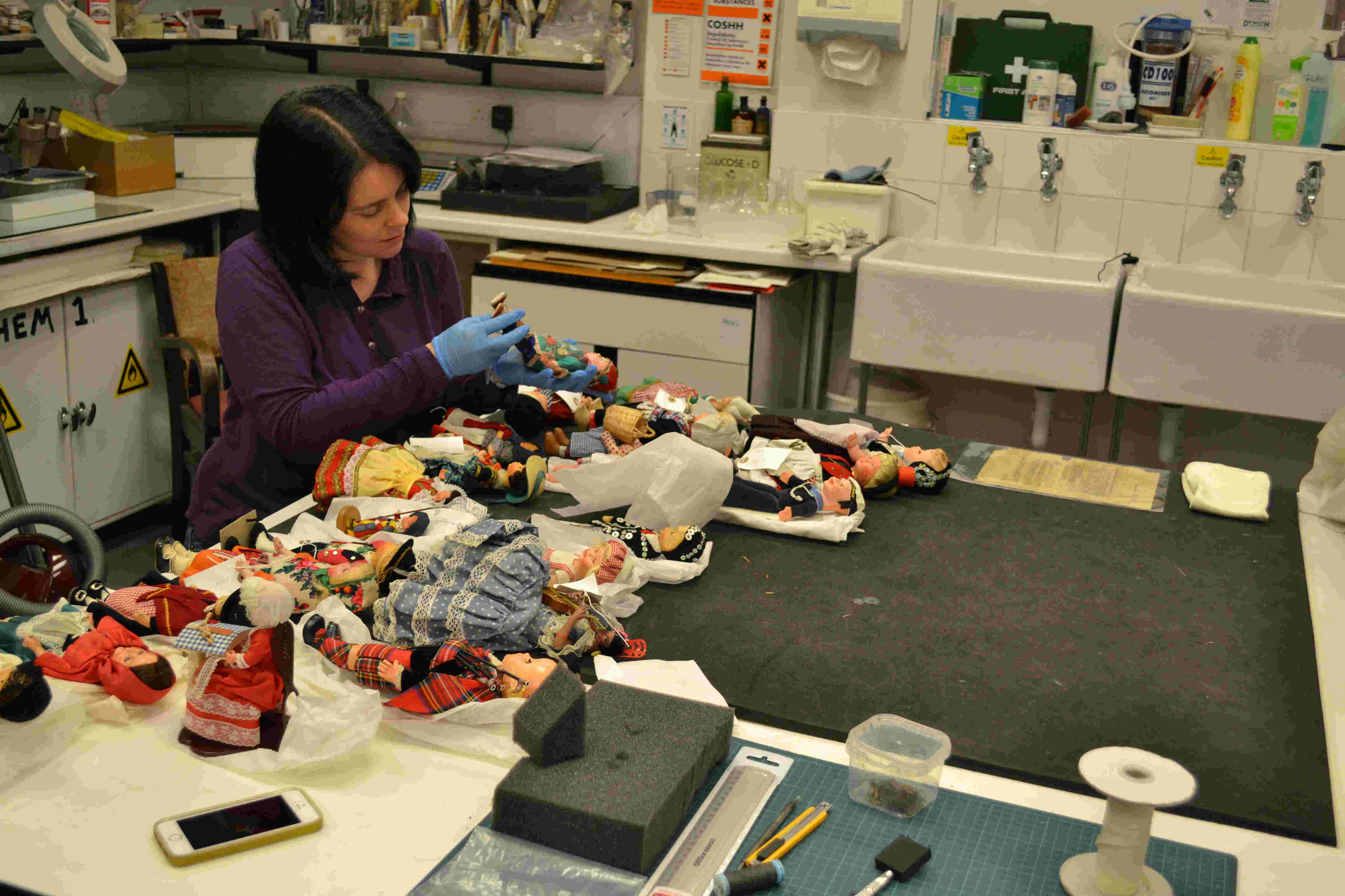 Collections Care Officer assessing costume dolls