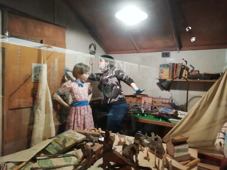 Curator works inside a display case next to a mannequin. The mannequin wears a pink floral dress with blue collar
