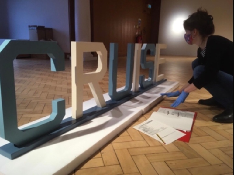 Curator wears blue gloves and kneels beside cut out lettering in blue and white spelling Cruise.
