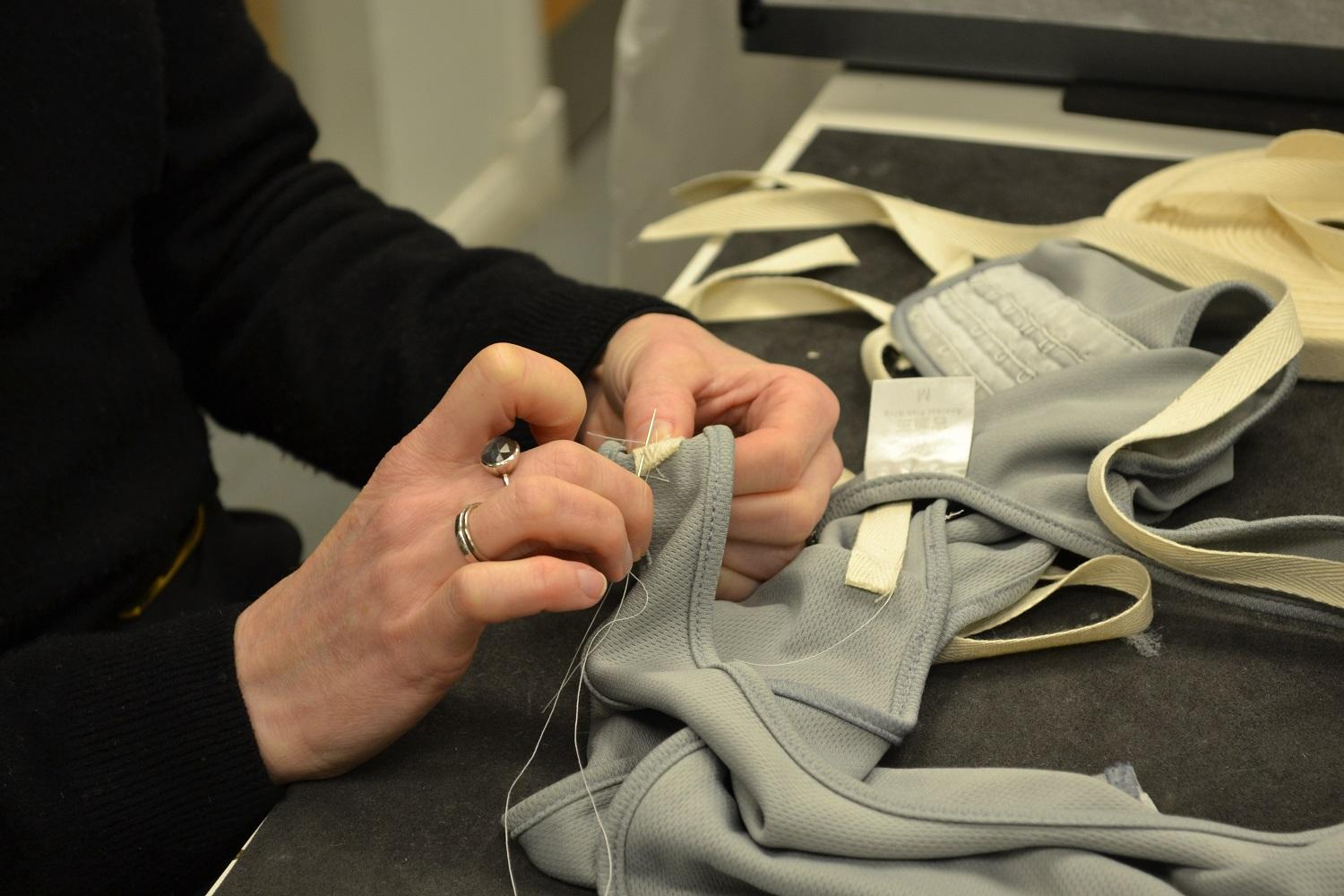 Curator stitching label onto textile object