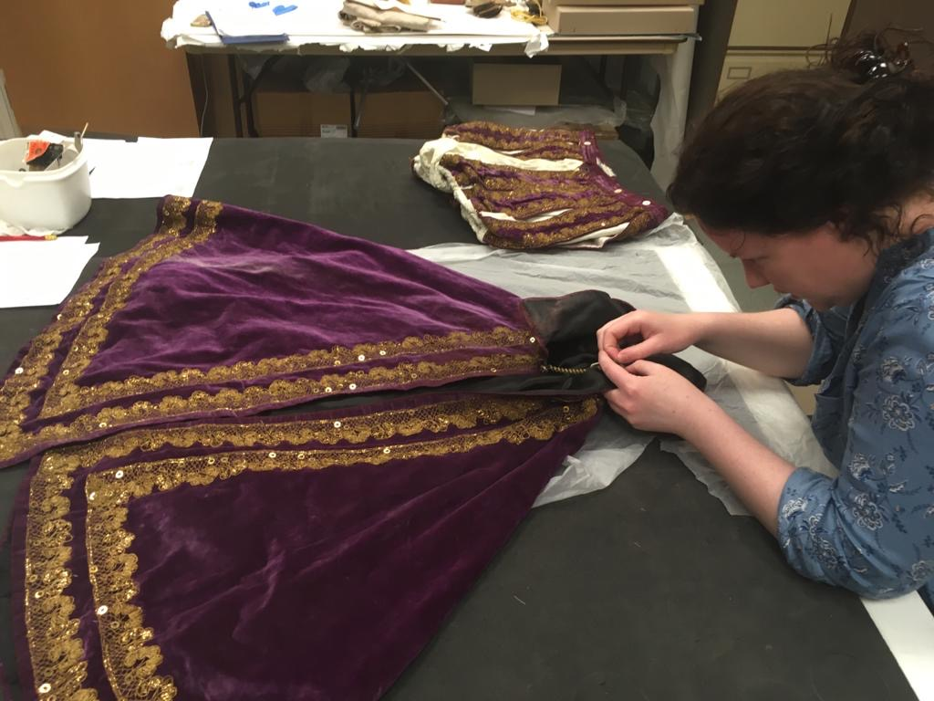 Volunteer Fran sewing a new accession label into a theatrical costume © City of Edinburgh Council Museums & Galleries; Museum of Edinburgh