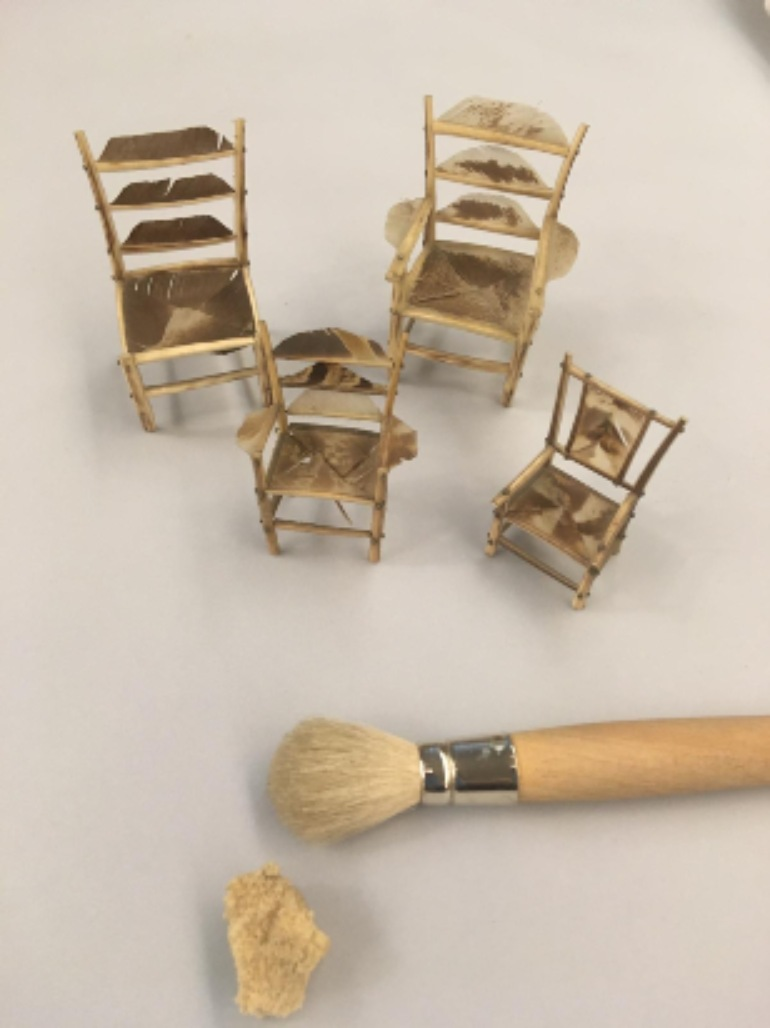 Four brown toy chairs with soft brush and sponge in the foreground