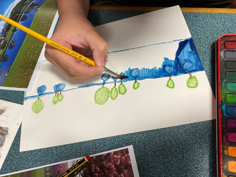 Photograph of child painting blues and greens on a white piece of paper. A colourful paint palette is next to the young artist