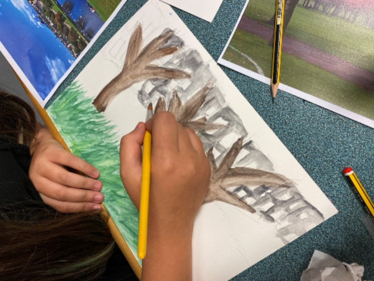Photograph of a child painting a picture of trees and grass on a white piece of paper