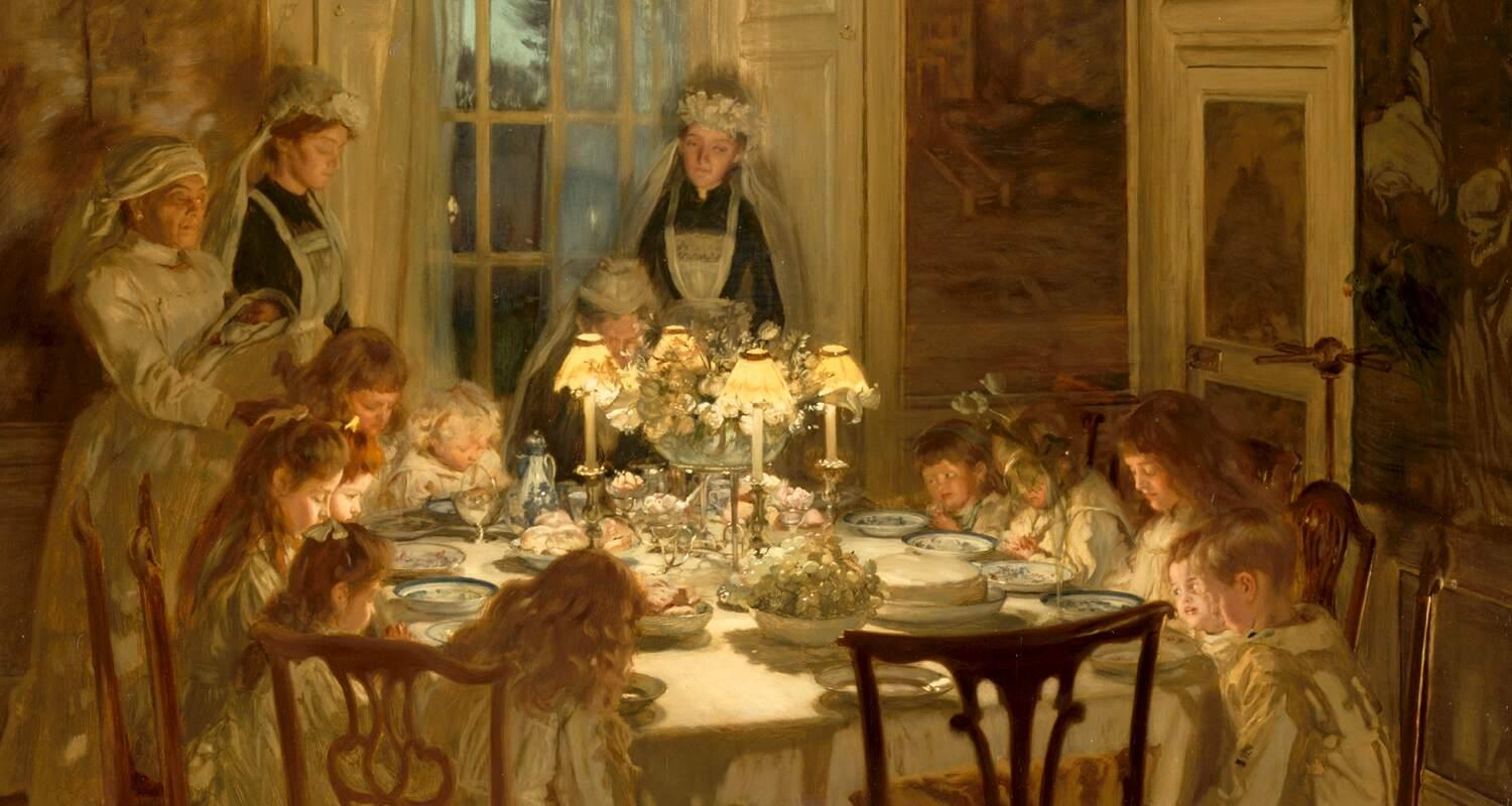 Edwardian children sitting round a dinner table with their maids