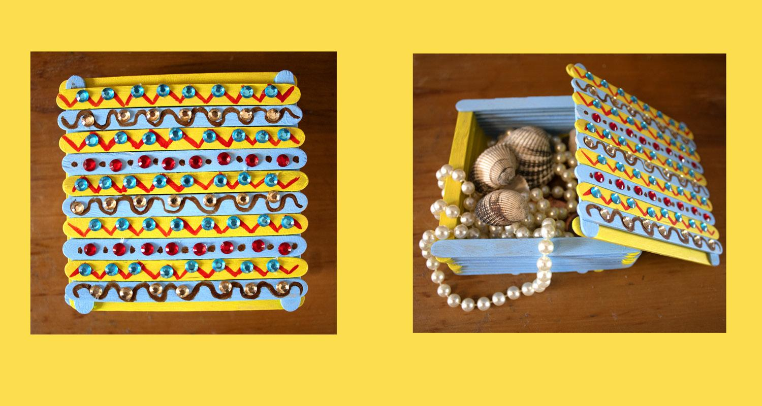 Pearls and shells inside a decorated treasure box in blue, red and yellow