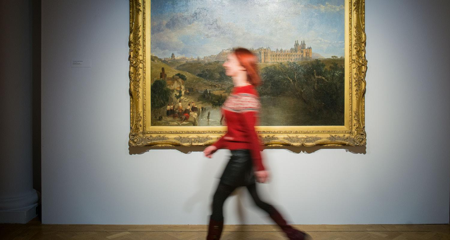 Woman walking past painting