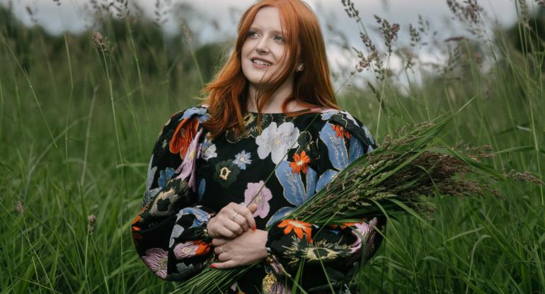 Ceitlin Lilidh sits in a green meadow wearing a black dress with large bold and colourful flowers