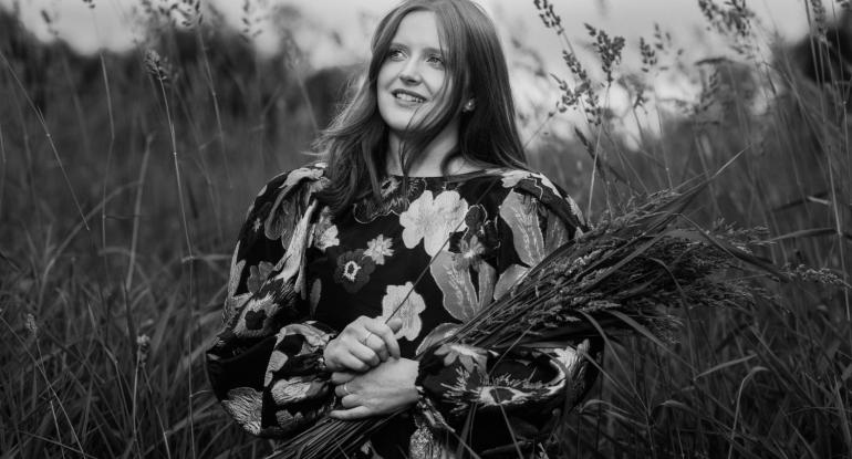 Black and white photograph of Ceitlin Lilidh in a meadow