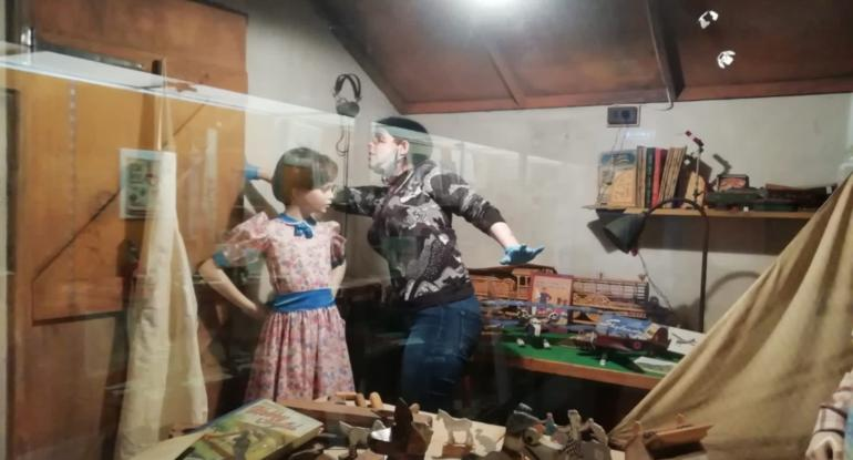 Curator working inside a display case beside a mannequin