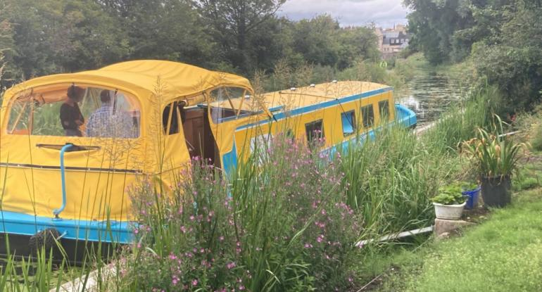 Yellow and blue long boat sitting on a canal surrounded by greenery. Part of the Museums & Galleries Edinburgh Discover Lothian project.