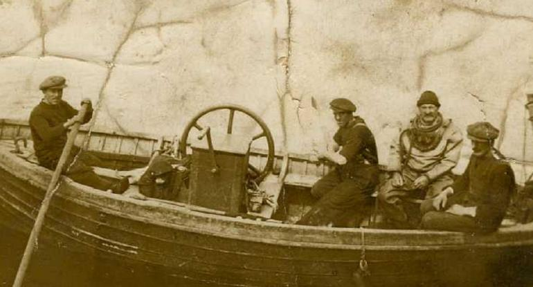 Sepia photograph of four men in a boat, one in a full diving suit.