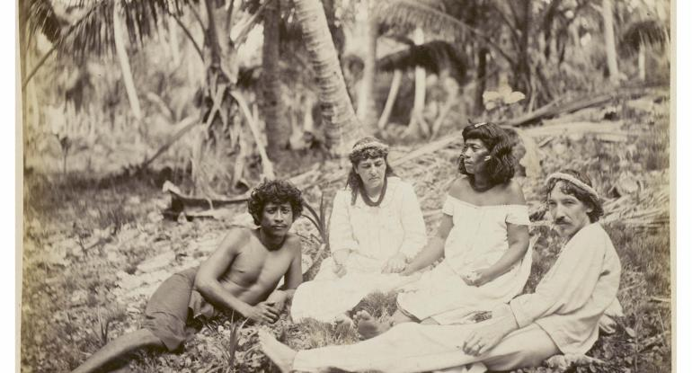 Robert Louis Stevensons in company with Nantoki and Natakauti, Butaritari. Group comprising of Nantoki, Fanny Stevenson holding hands with Natakauti, and Robert Louis Stevenson; the men are reclining, the women sitting, on the ground.
