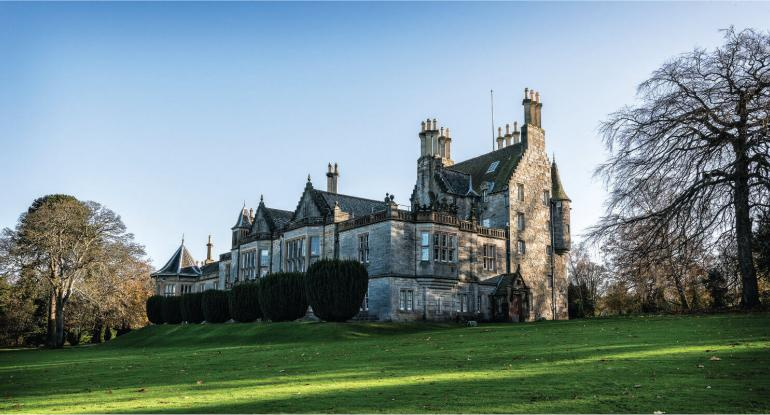 Lauriston Castle on a sunny day surrounded by trees and greenery
