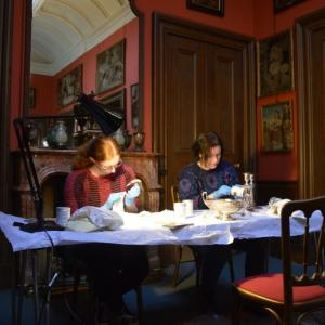 Two volunteers sitting in the dining room of Lauriston Castle polishing silver objects from the collection