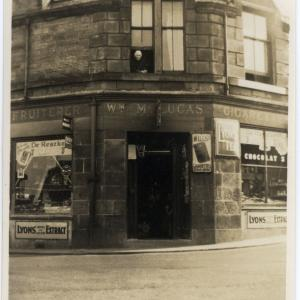 At the corner of Hopetoun, Bo'ness and Shore Roads, (left) William McLucas's shop with Granny Dalgleish, a midwife, looking out of the window. Today, home to Deery Funeral Services, with some alterations to the building visible. © CEC Museums & Galleries