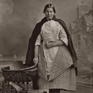 Thomas V. Begbie, Studio portrait of Newhaven fishwife, standing beside wicker creels, plate negative: c. 1857-1860 The Cavaye Collection of Thomas V. Begbie Prints. City Art Centre, Museums & Galleries Edinburgh